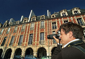 Mathieu Facq taking pictures of building façades in place des Vosges, Paris