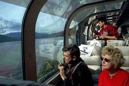 "Passengers admiring the Alberta scenery from the Rocky Mountaineer's ""dome car.""."