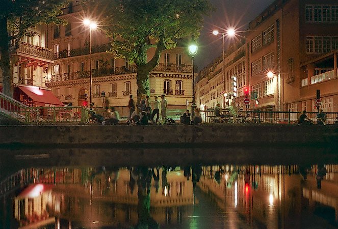 people hanging out along canal saint martin on a summer evening. Black Bedroom Furniture Sets. Home Design Ideas